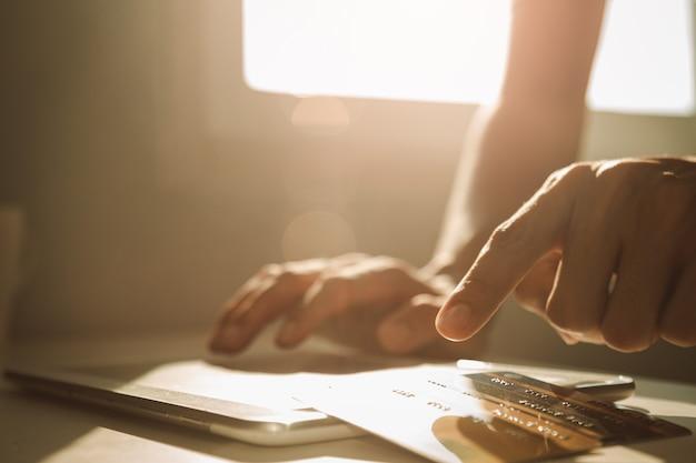 Mannelijke handen gebruikend tabletcomputer en kiezend creditcard