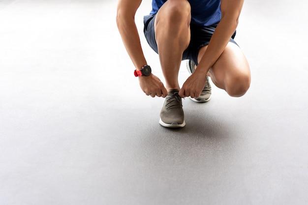 Mannelijke handen gelijkmakende schoenveter op loopschoenen vóór de praktijk.