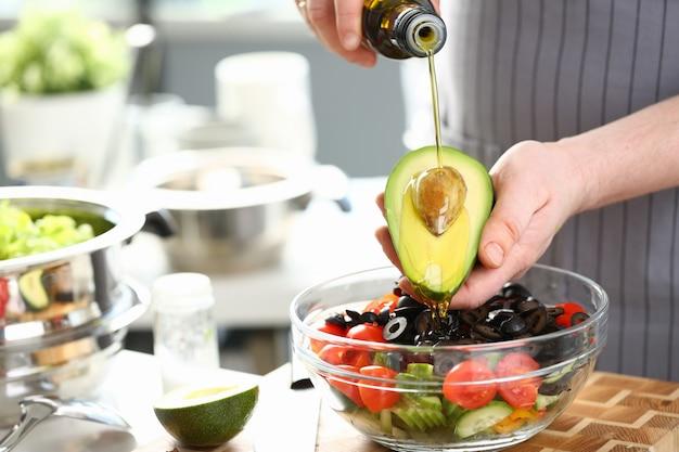 Mannelijke handen gieten olie gehalveerde tropische avocado