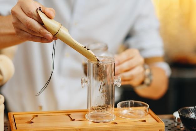 Mannelijke handen goten de droge bladeren van groene thee in transparant glas