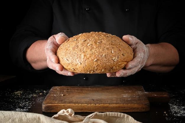Mannelijke handen houden bruin gebakken roggebrood