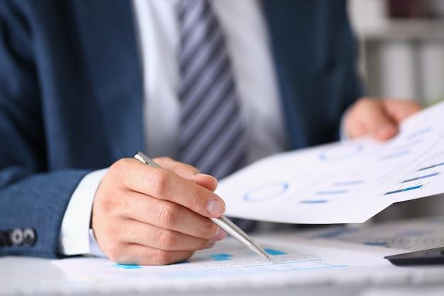 Mannelijke handen houden documenten vast met financiële statistieken
