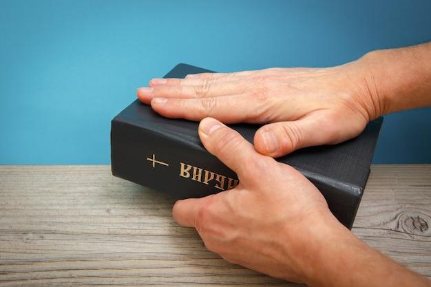 Mannelijke handen houden een bijbel leunend op een houten tafel boektitel vertaling holly bible