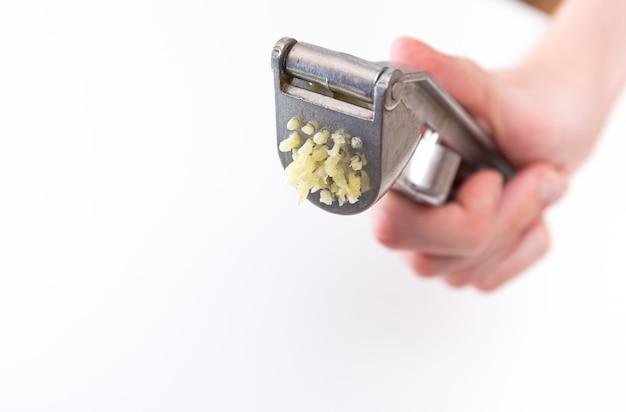 Mannelijke handen houden een knoflookpers of knoflookpers vast. kitchen tool voor het bereiden en bereiden van salades, gerechten.