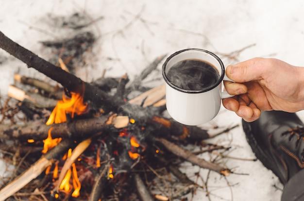 Mannelijke handen houden een mok koffie bij een brandend kampvuur.