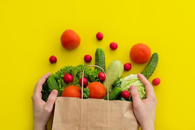 Mannelijke handen houden een papieren zak met producten, groenten. voedsellevering.