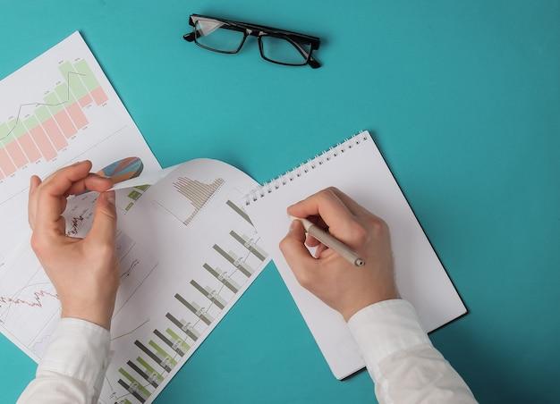 Mannelijke handen houden een pen en grafieken vast, een bril op een blauwe achtergrond. bovenaanzicht
