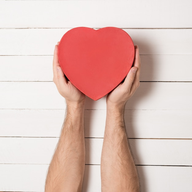 Mannelijke handen houden een rode hartvormige doos