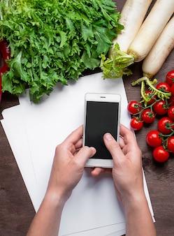 Mannelijke handen houden een smartphone op de keukentafel