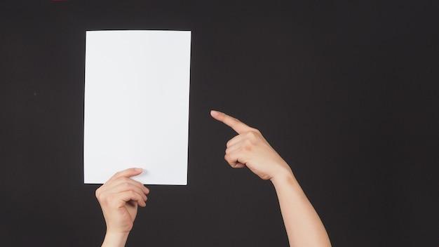 Mannelijke handen houden en wijzen met de vinger naar het a4-papier op zwarte achtergrond.