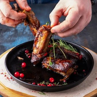 Mannelijke handen houden gegrilde varkensribbetjes. mens die geroosterde varkensvleesribben eet. detailopname