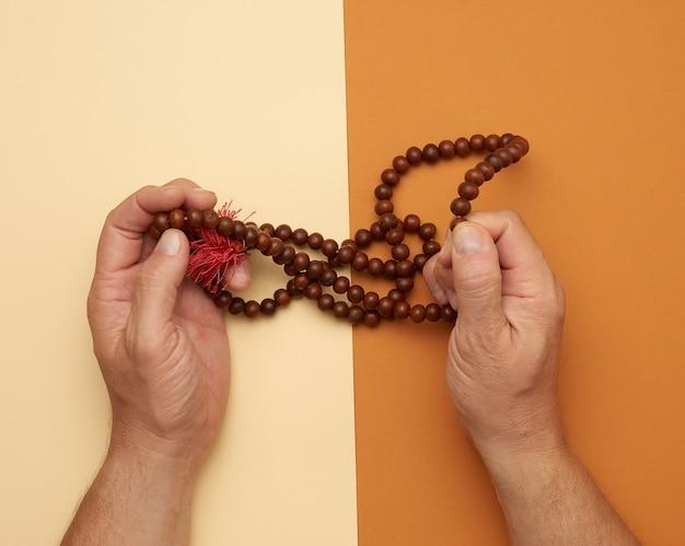 Mannelijke handen houden houten gebedskralen vast