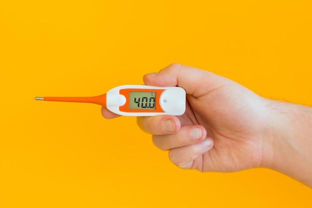 Mannelijke handen houdt thermometer met hoge temperatuur geïsoleerd op een gele muur. thermometer dicht omhoog. gezond leven, virus covid 19 concept