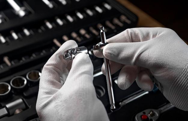 Mannelijke handen in handschoenen over open gereedschapskist met verschillende metalen gereedschappen voor auto- en huisreparatie, close-up.