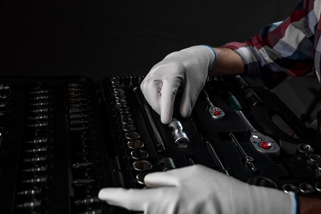 Mannelijke handen in witte bouwhandschoenen over open toolkit met verschillende metalen gereedschappen voor auto- en huisreparatie, close-up.