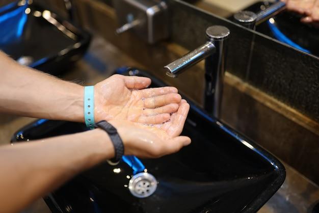 Mannelijke handen in zeepachtig schuim onder stromend water