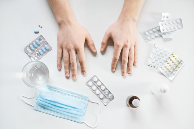 Mannelijke handen liggend op de tafel met tabletten medicijnen en medicijnen voor behandeling en een chirurgisch masker.