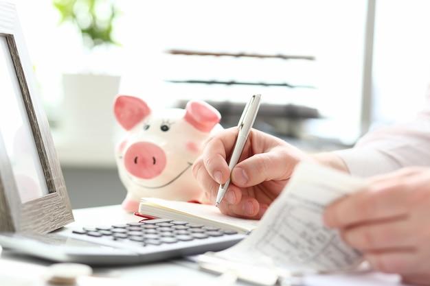 Mannelijke handen maken van aantekeningen met zilveren pen over gezinsbudget