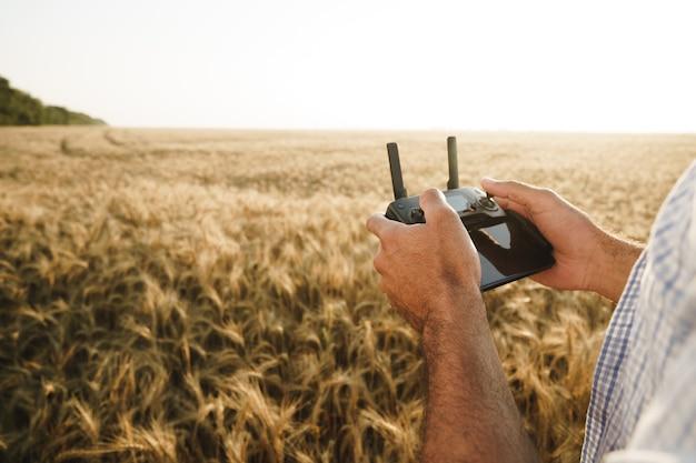 Mannelijke handen met afstandsbediening van quadcopter in tarweveld
