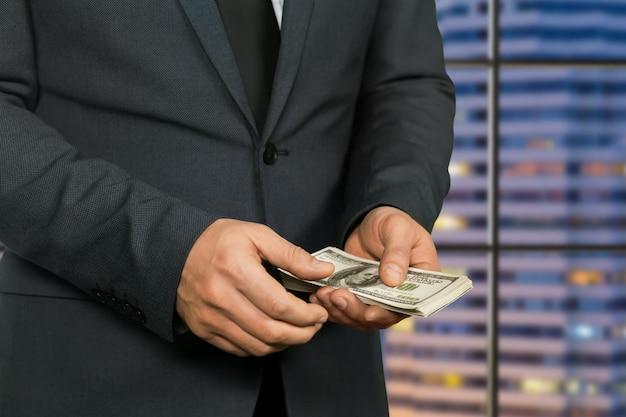 Mannelijke handen met amerikaanse dollars. rijke zakenman op wolkenkrabberachtergrond. handen van crimineel. ver van de ogen van de wet.
