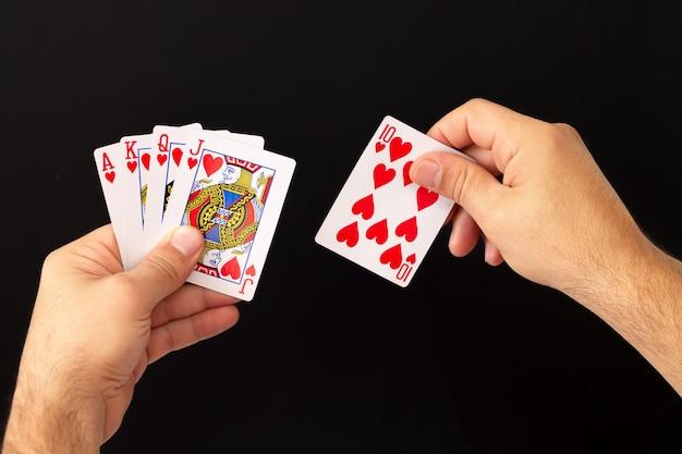 Mannelijke handen met combinatie van royal flush pokerkaarten op donkere achtergrond
