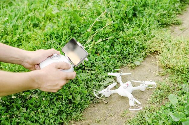 Mannelijke handen met een afstandsbediening met een smartphone van een quadrocopter op het gras en drone