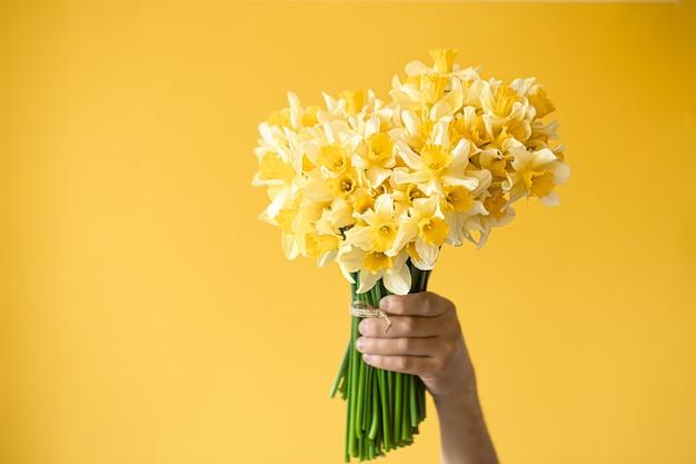 Mannelijke handen met een boeket gele narcissen.