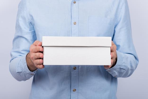 Mannelijke handen met een kartonnen doos. vooraanzicht. express levering. postbode bracht pakket