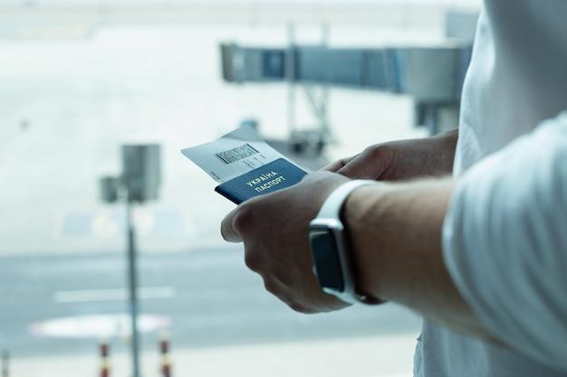 Mannelijke handen met een paspoort en kaartjes op de achtergrond van de luchthaven