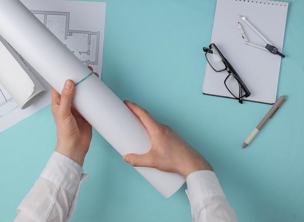 Mannelijke handen met een rol papier op een blauwe achtergrond, daarnaast zijn tekeningen, kompassen, een notitieboekje en een bril. bovenaanzicht