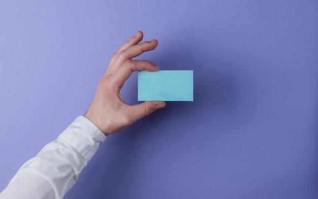 Mannelijke handen met een visitekaartje paarse achtergrond. ruimte voor een idee. bovenaanzicht