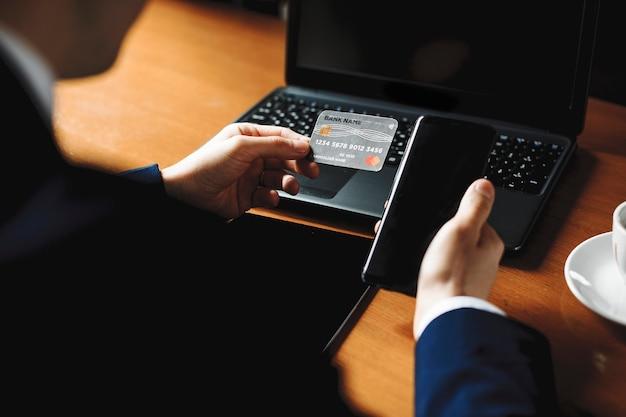 Mannelijke handen met een zilveren creditcard en een smartphone zittend op tafel met een laptop erop.