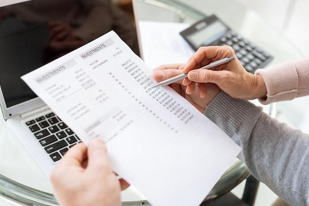 Mannelijke handen met financieel document terwijl zijn vrouw met pen wijst op som geld dat werd uitgegeven voor huishoudelijke behoeften