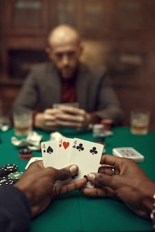 Mannelijke handen met kaarten, pokerspeler in pak