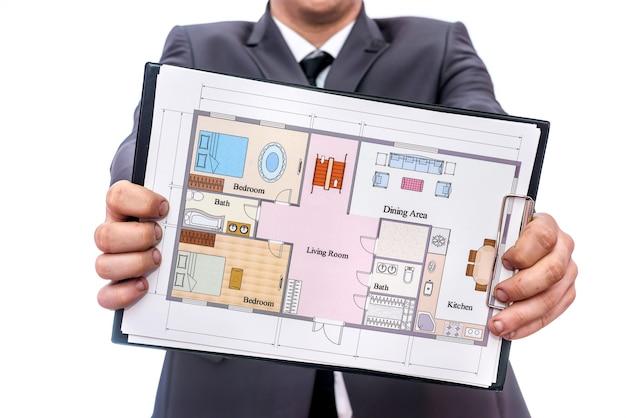Mannelijke handen met klembord en huisplan erop
