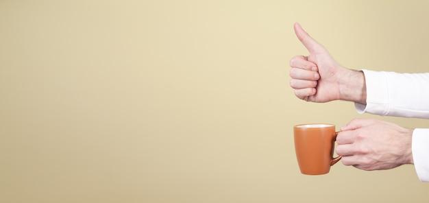 Mannelijke handen met kopje koffie en duim opdagen op gele achtergrond.