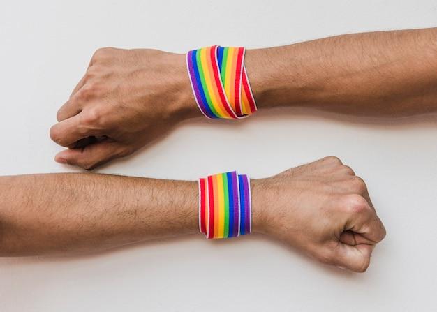 Mannelijke handen met linten in lgbt-kleuren