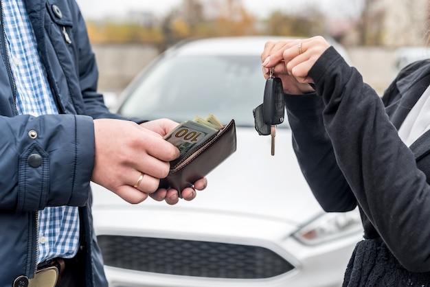 Mannelijke handen met portemonnee en vrouwelijke handen met sleutels van auto