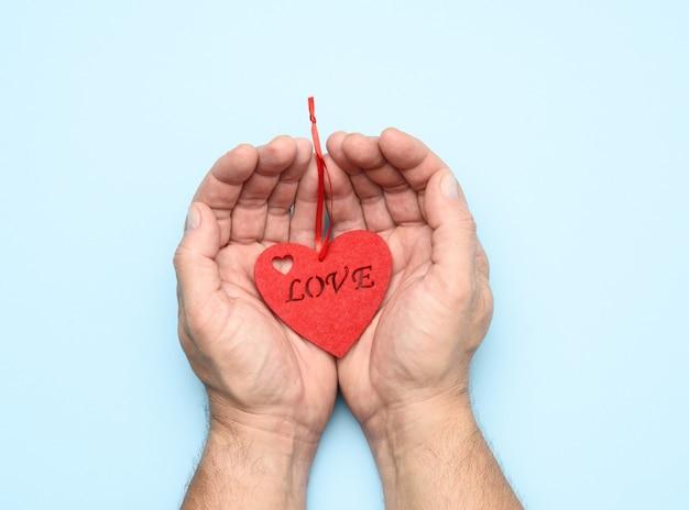 Mannelijke handen met rood hart op een blauw
