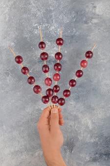 Mannelijke handen met stokken van rode druiven op marmeren oppervlak.