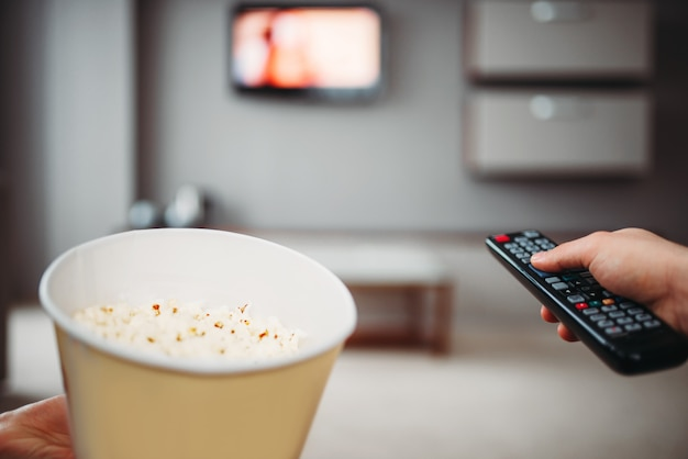 Mannelijke handen met televisie-afstandsbediening en popcorn tegen tv aan de muur.