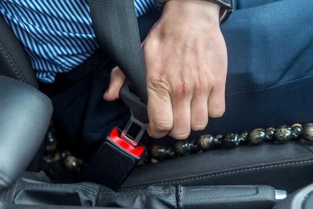 Mannelijke handen met veiligheidsgordel in auto close-up