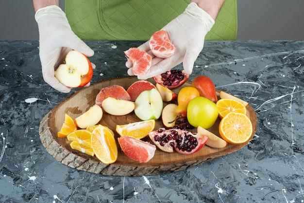 Mannelijke handen met vers fruit op marmeren tafel.