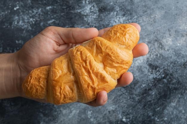 Mannelijke handen met verse croissant op marmeren achtergrond