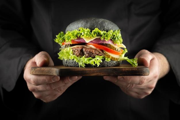Mannelijke handen met verse heerlijke zwarte rundvlees hamburger man in het zwarte uniform van de chef-kok
