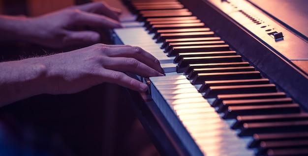 Mannelijke handen op de piano toetsen close-up van een prachtige kleurrijke achtergrond, het concept van muzikale activiteit