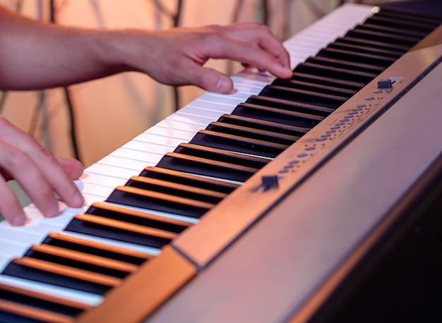 Mannelijke handen op de toetsen van een piano