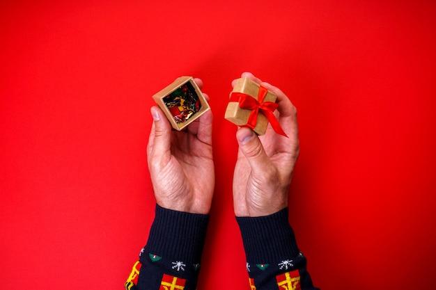 Mannelijke handen op rood opent een kerstcadeau