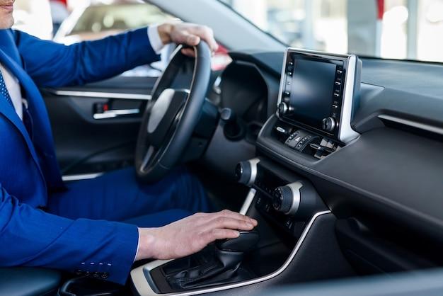 Mannelijke handen op stuur, auto-interieur