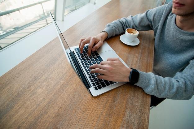 Mannelijke handen op toetsenbord van moderne laptop. freelance-concept. programmeur concept. gesneden weergave van jonge man aan het werk op de computer bij het raam met een kopje espresso voor hem.